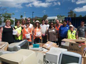 Group standing around donated waste computer equipment