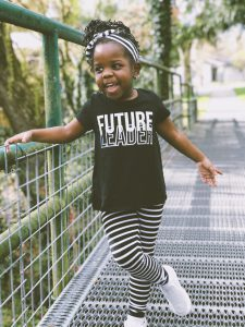 "Child wearing a t-shirt that says ""Future Leader"" on it."